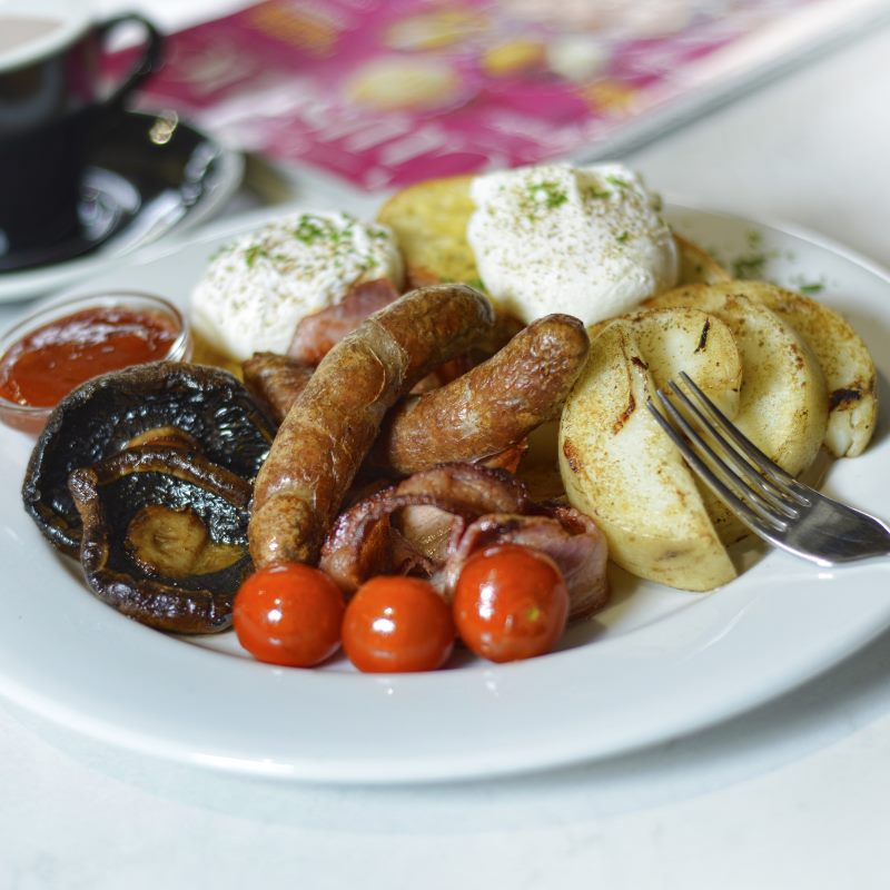 A plate of sausages, potatoes, mushroom, bacon, and tomato